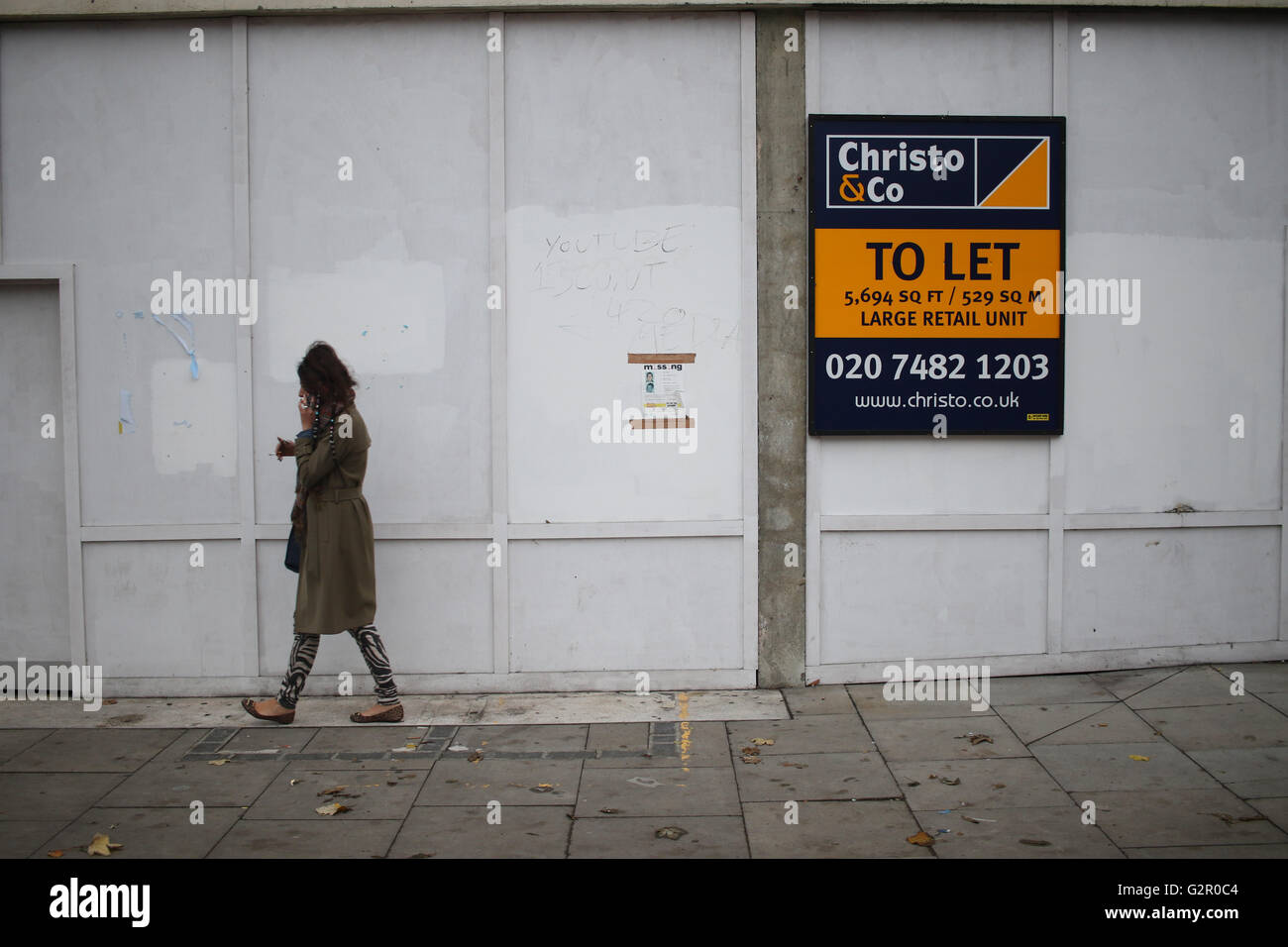 Woman talking on mobile phone walks past whitewashed wooden walls and estate agent's To Let sign. - Stock Image