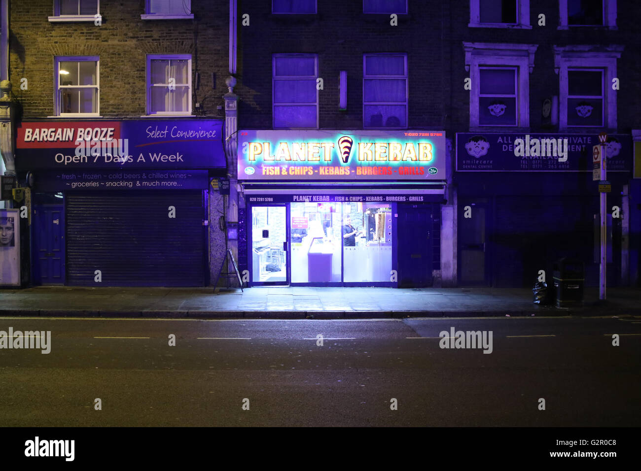 Shop frontages of a kebab shop and alcohol shop - Stock Image