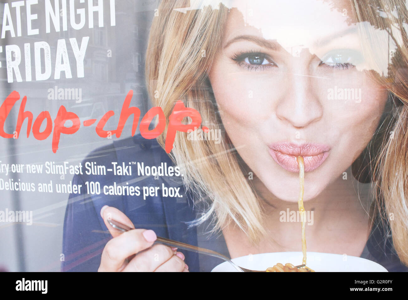 London street reflected in advert for noodles featuring woman - Stock Image