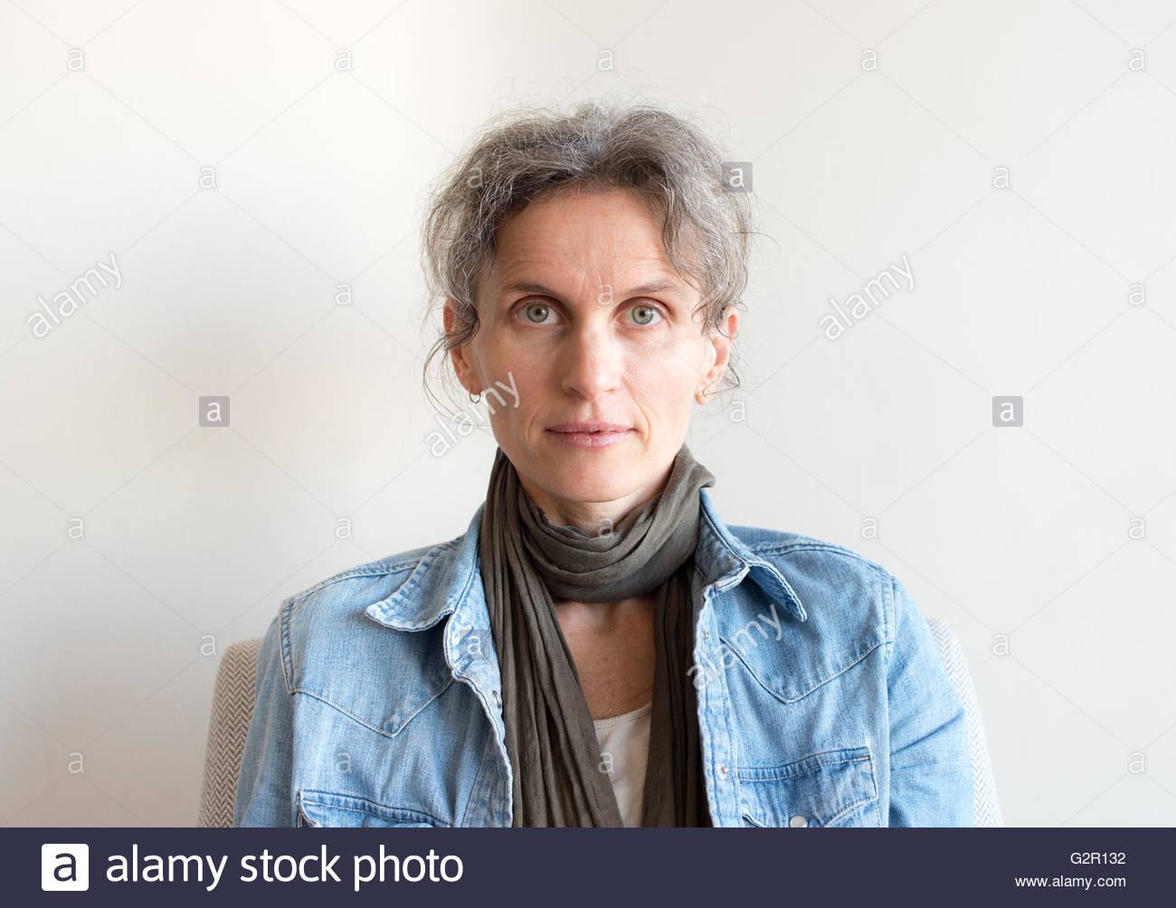 Portrait of middle aged woman with grey hair, denim shirt and scarf - Stock Image