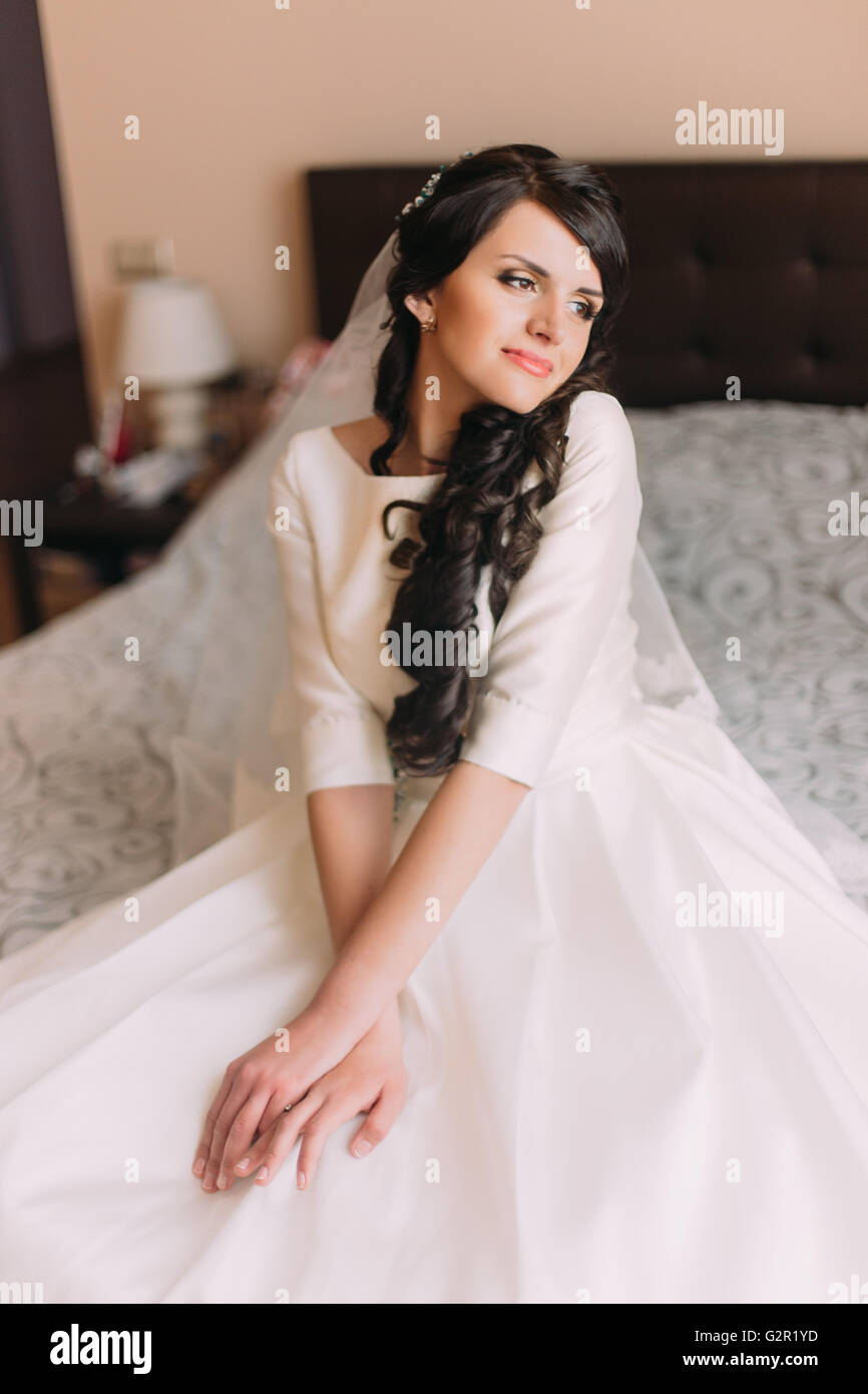 Young Fashionable Excited Bride Sitting On Bed In Wedding Dress And