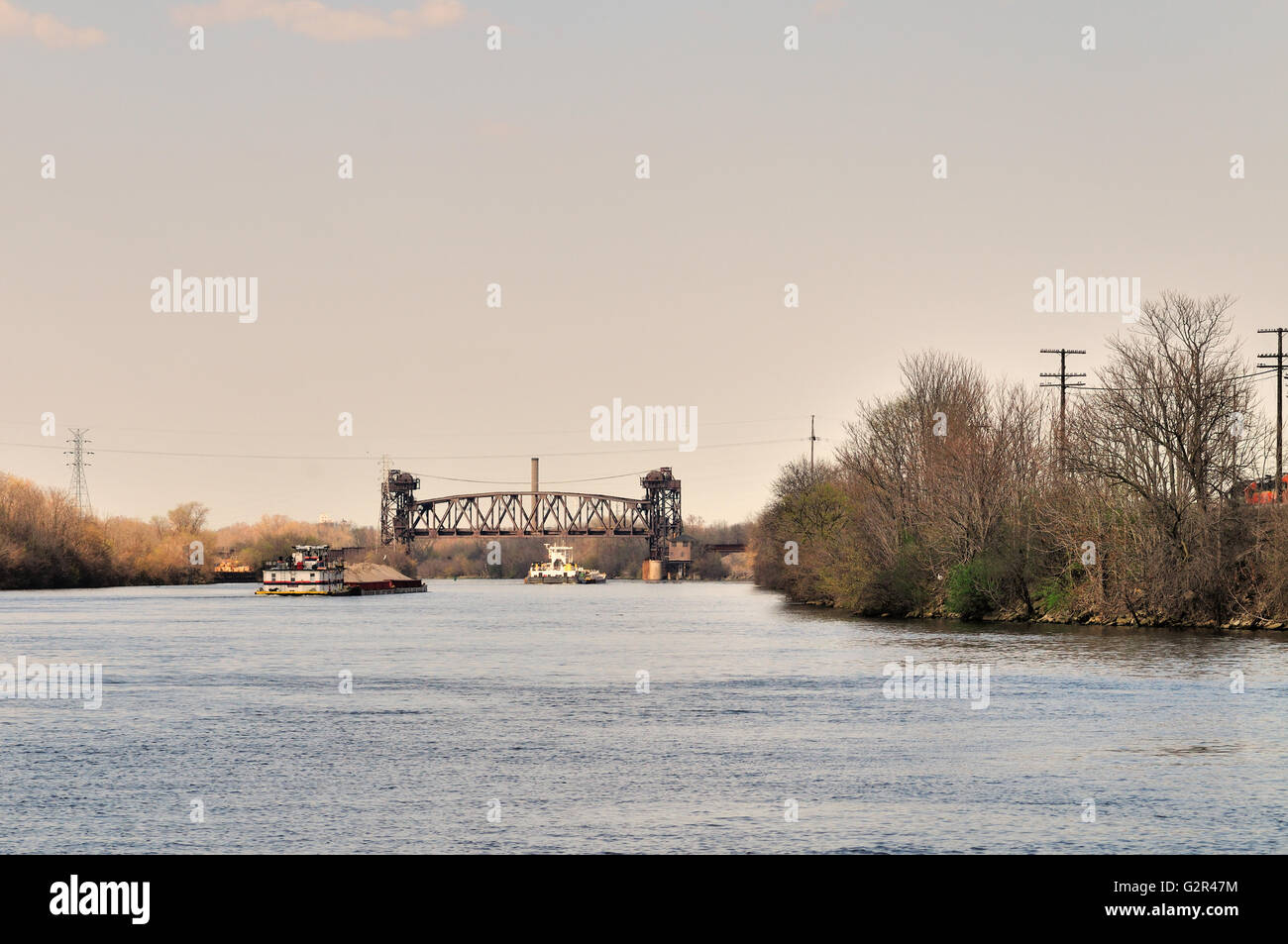 Traffic heading towards a railroad vertical-lift bridge on the Des Plaines River in Joliet, Illinois. - Stock Image