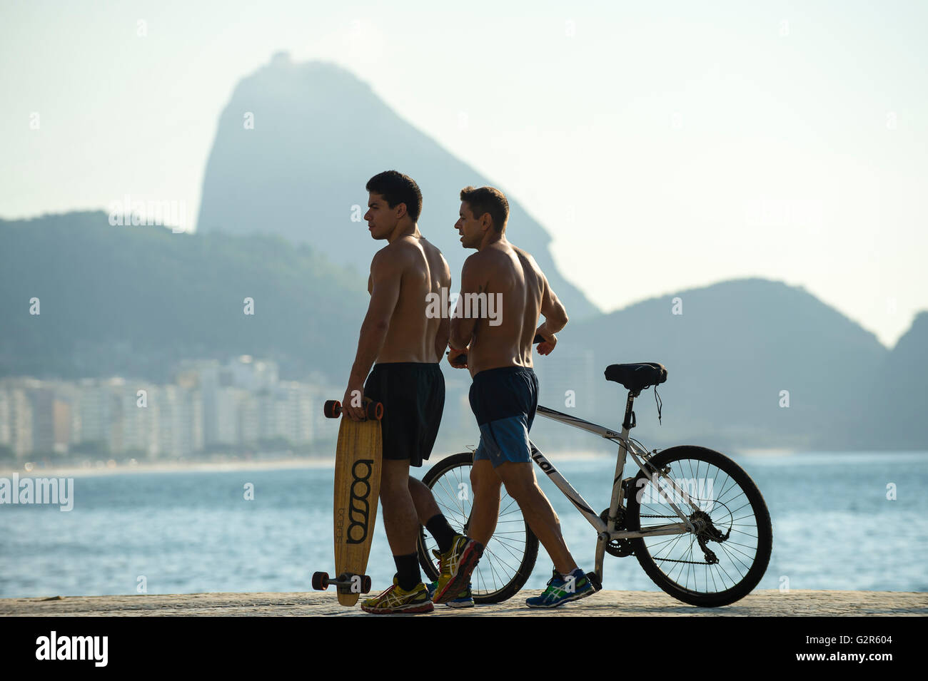 RIO DE JANEIRO - APRIL 3, 2016: Young carioca Brazilian men walk with bicycle and skateboard on the beachfront boardwalk. - Stock Image