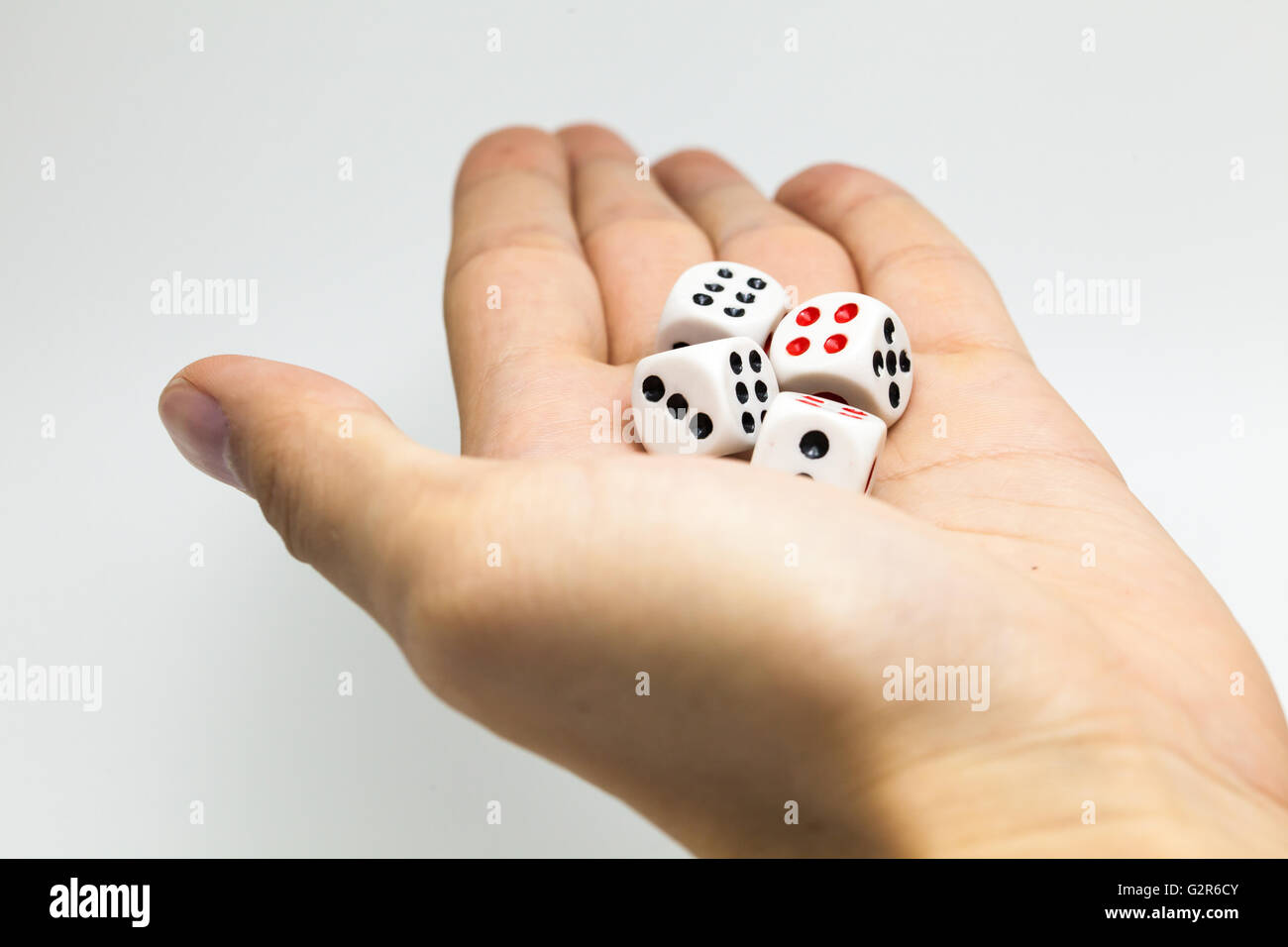 Human hand ready to roll the dice on white isolated background - Try luck, Take Risk or Business concept (Focus Stock Photo