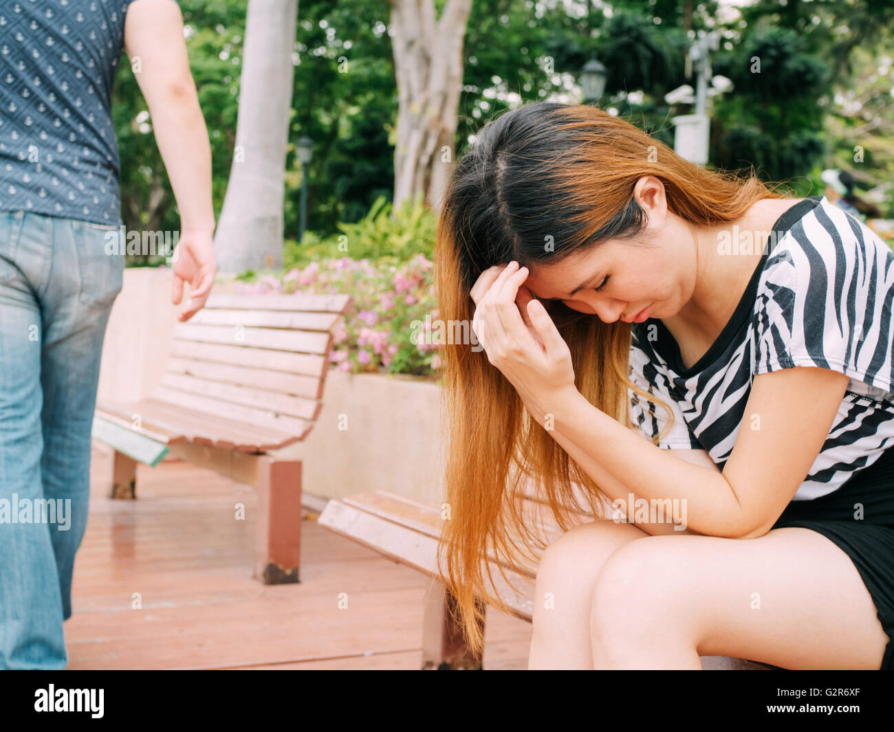 Breakup of a couple with sad girlfriend and boyfriend walking away with city in the background - Stock Image