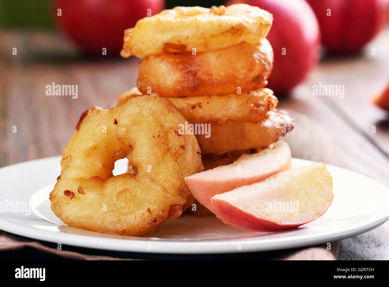 Apple rings on white plate - Stock Image