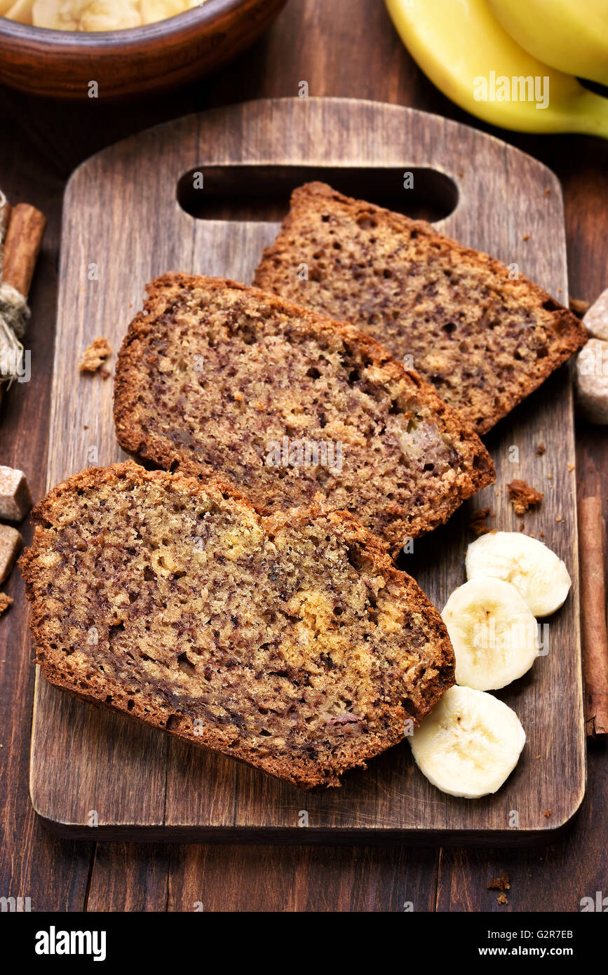 Slices of banana bread on wooden cutting board, top view - Stock Image