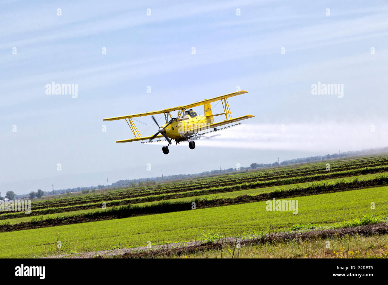Turbo Prop Bi-Wing Crop Duster applying chemicals to rice paddy. - Stock Image