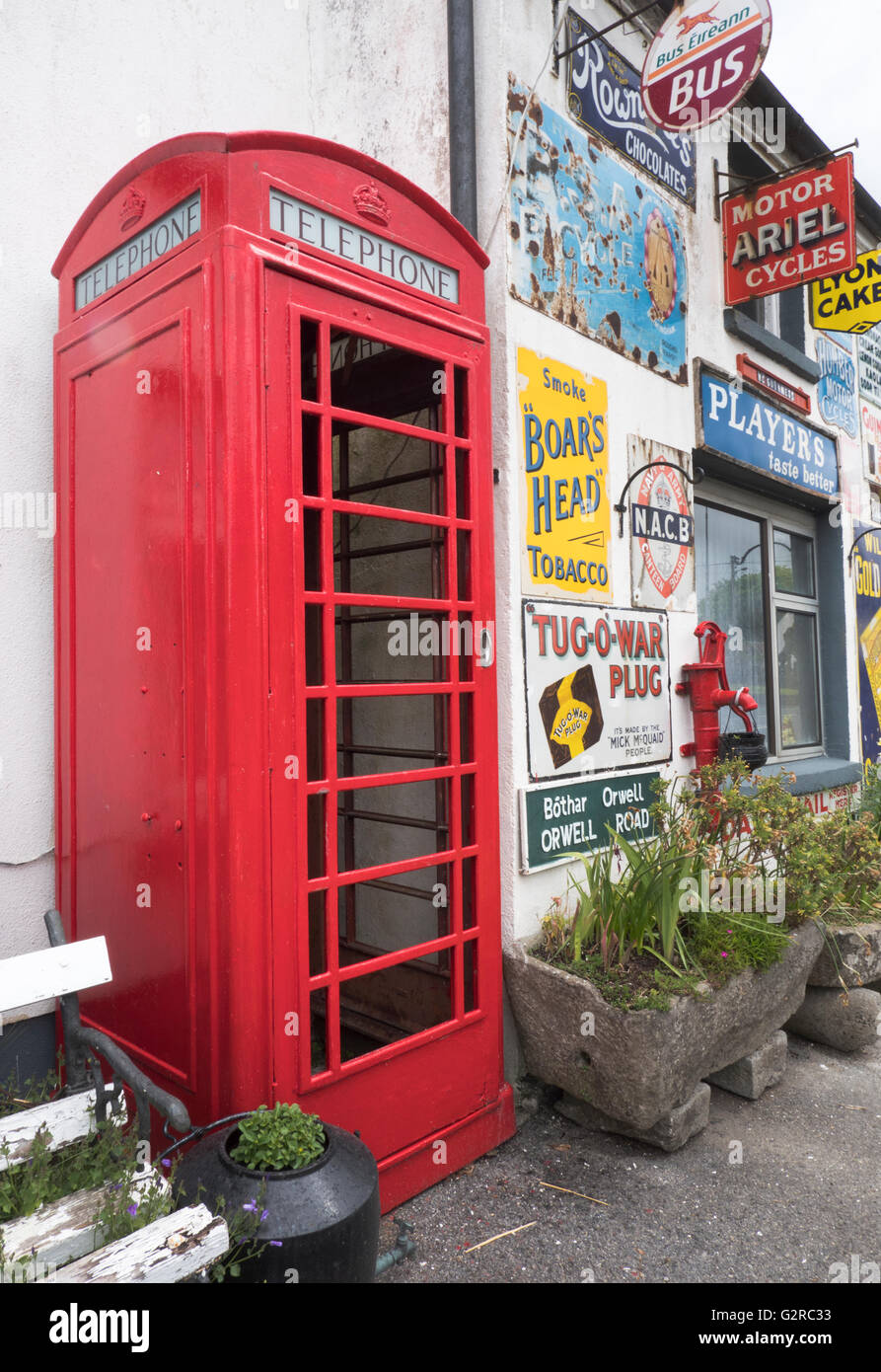 Building covered with tin advertising signs including a K6 telephone kiosk at Horseleap, County Offaly, Southern - Stock Image