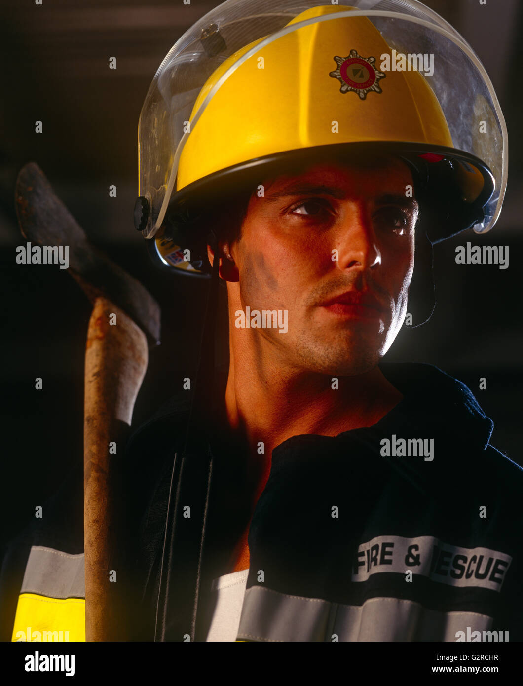Man in a firefighter outfit, indoors. - Stock Image