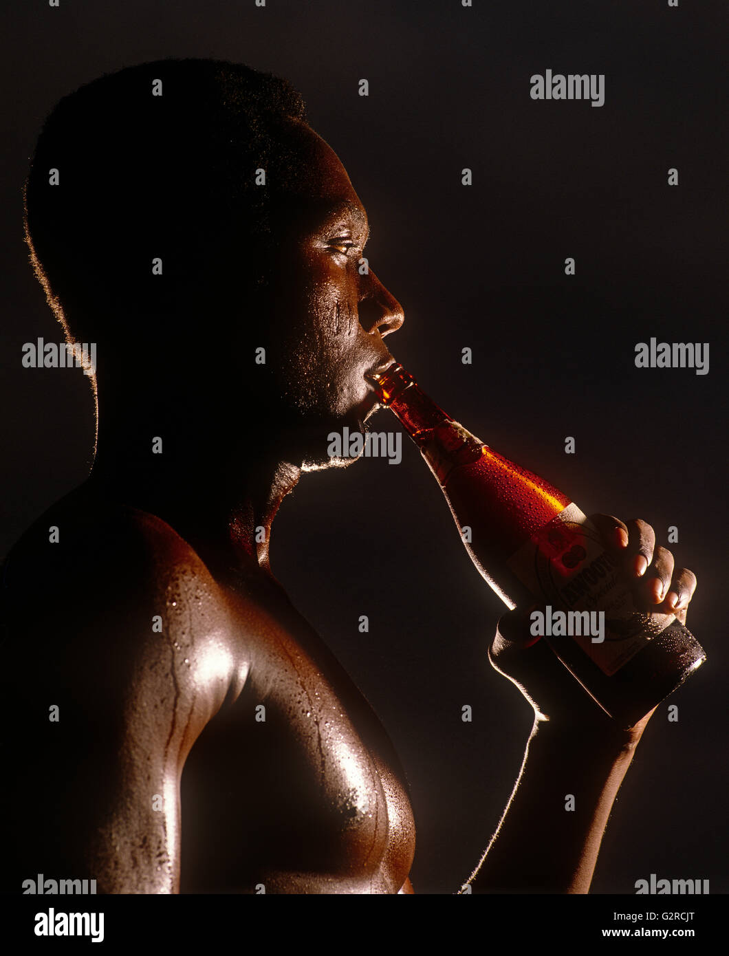 A man drinking a bottle of alcohol, indoors. - Stock Image