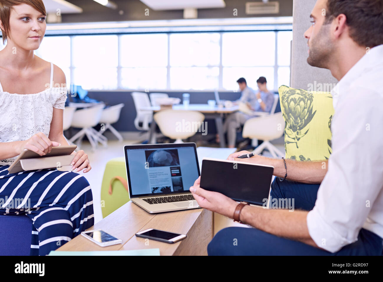Woman holding tablet while paying attention to male business partner - Stock Image