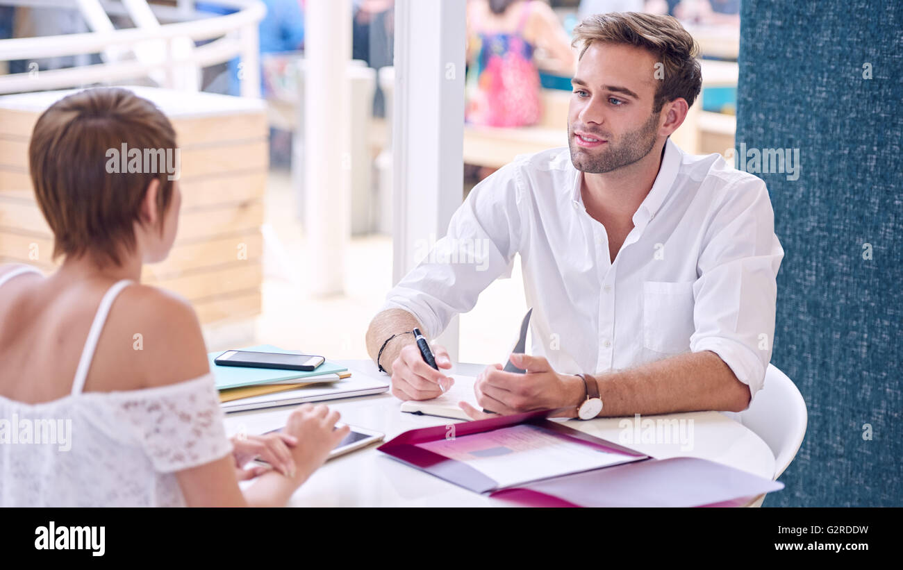 Male tutor mentoring female student in co-work space - Stock Image