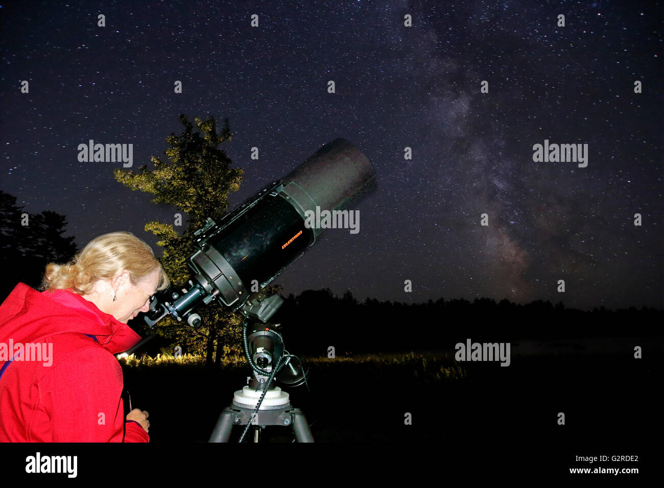 A woman looking at the stars and planets through a telescope - Stock Image