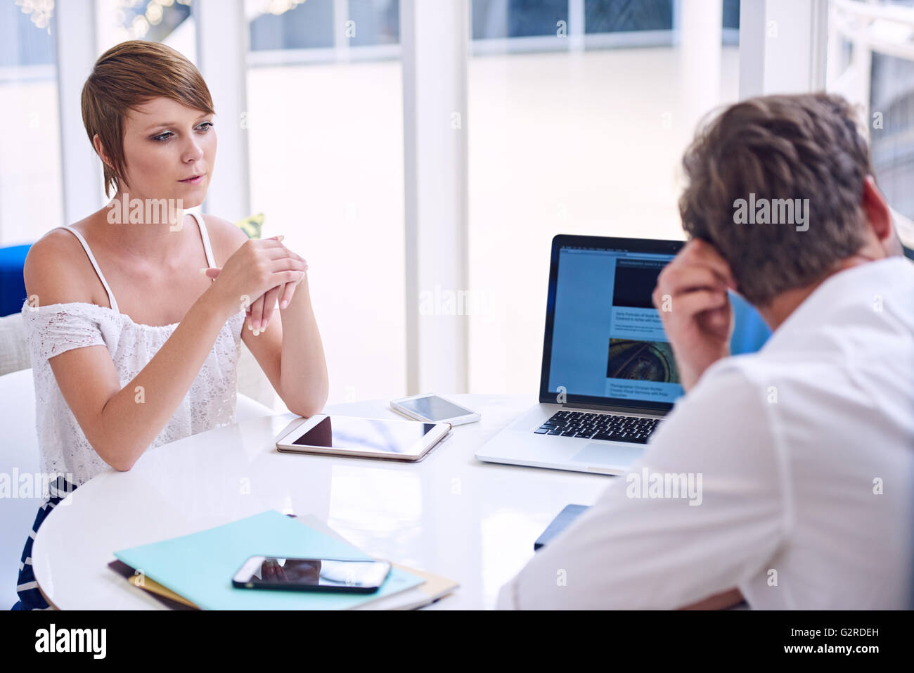 Apparent disagreement between male and female partners during business meeting - Stock Image