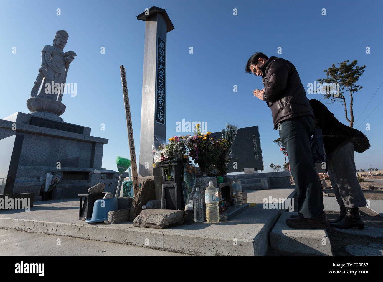 People come to pray and remember the victims of the tsunami at Arahama cenotaph on the seawall near Sendai, Miyagi, - Stock Image