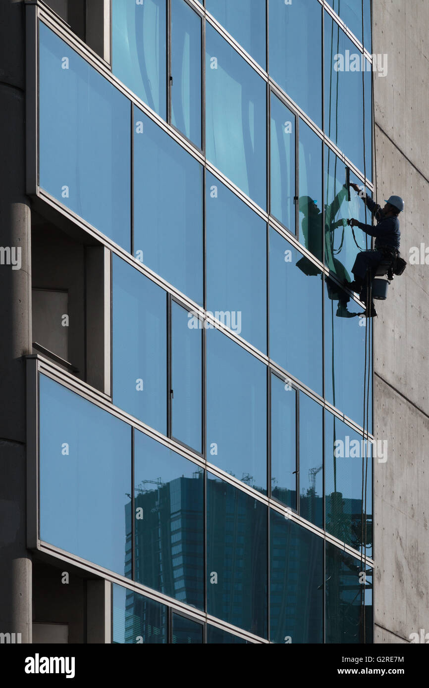 Rope access technician cleans windows on a building near Zoshigaya, Tokyo, Japan. Friday January 15th 2016 Stock Photo