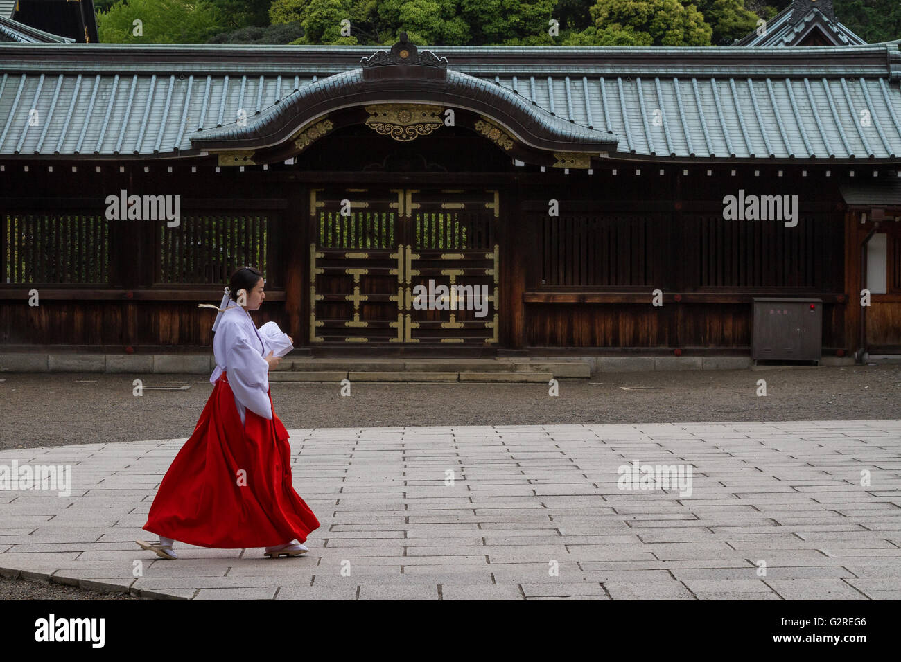 A shrine maiden in red and white robes crosses a courtyard at the controversial Yasukuni Shrine in Kudanshita, Tokyo, - Stock Image