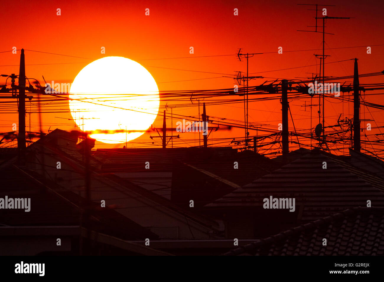 Sunset over rooftops and TV aerials in suburban Tokyo. Tsukushino, Tokyo, Japan. Saturday May 21st 2016 - Stock Image