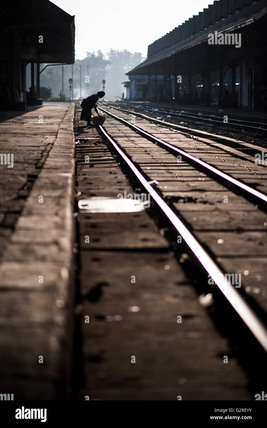 A garbage collector working at the rail tracks of the Yangon Central Train Station, Myanmar. - Stock Image