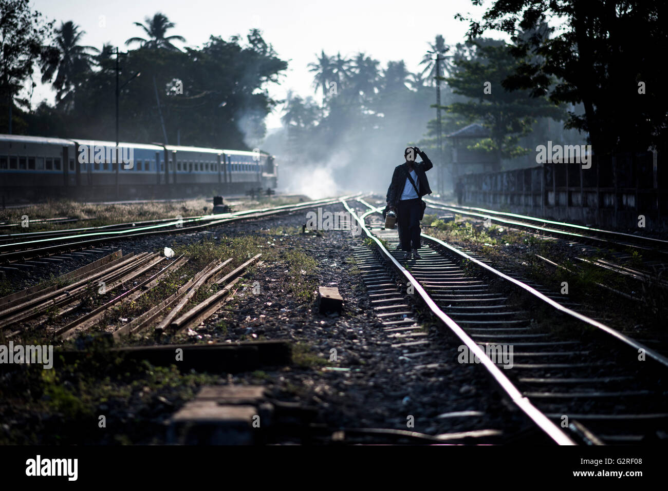 A man walks on the Rail tracks of the Yangon Central Train Station, Myanmar. - Stock Image