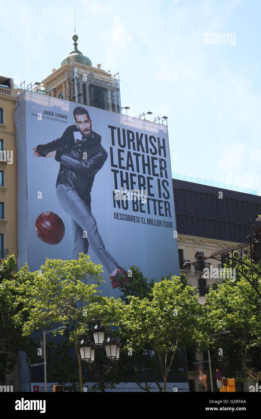 Turkey footballer Arda Turan of FC Barcelona adorns a giant advertising poster in the centre of the Spanish city. - Stock Image