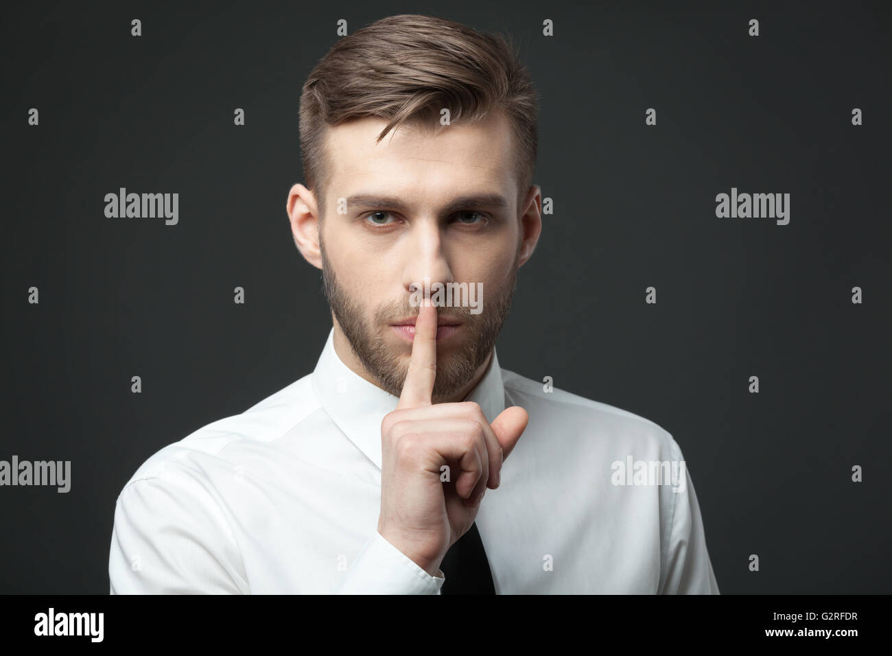 """Keep your secrets! Studio portrait of young handsome businessman gesturing """"shh"""" to the camera. Stock Photo"""