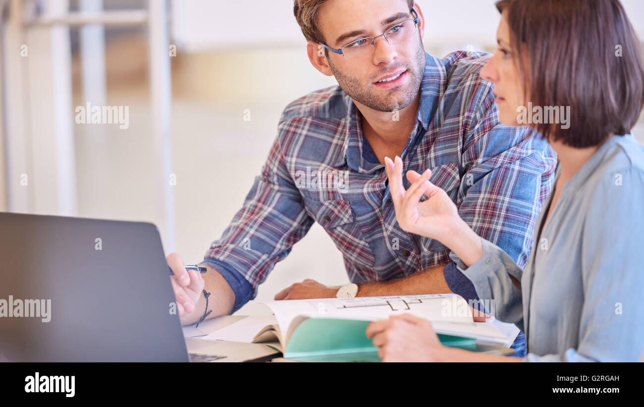Designer having a meeting with freelance production associate - Stock Image