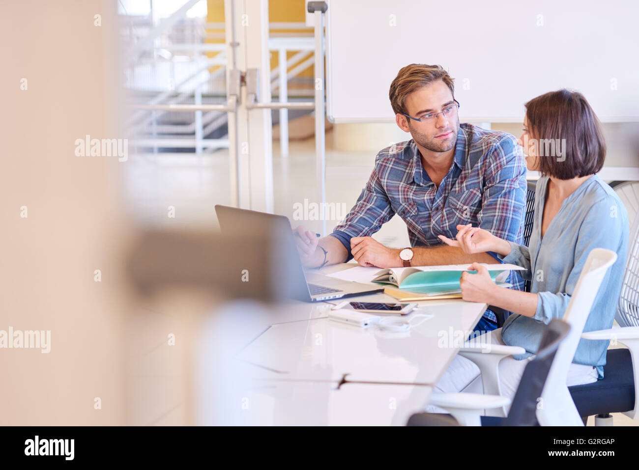 Business man and woman working together in conference room - Stock Image