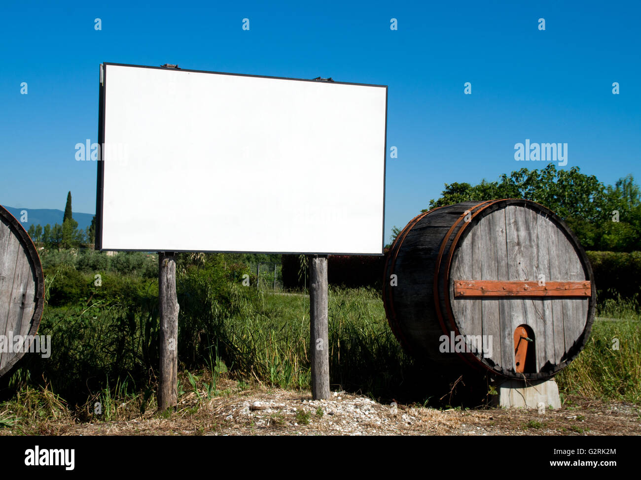 blank billboard in the countryside cultivated with traditional wooden barrel - Stock Image