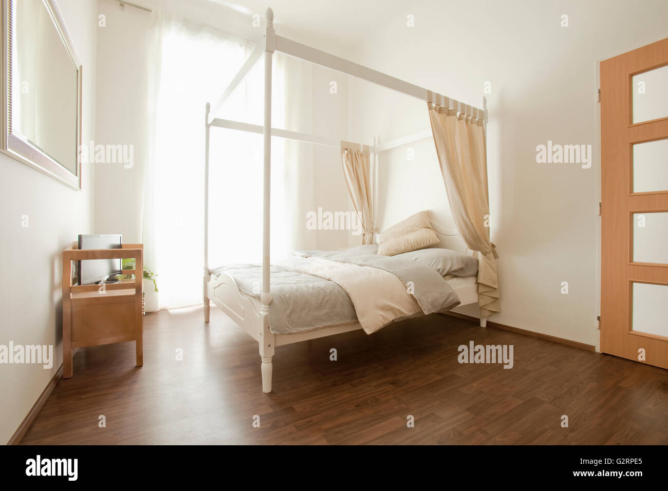 Apartment Interior- Bedroom with Four Poster Bed. - Stock Image