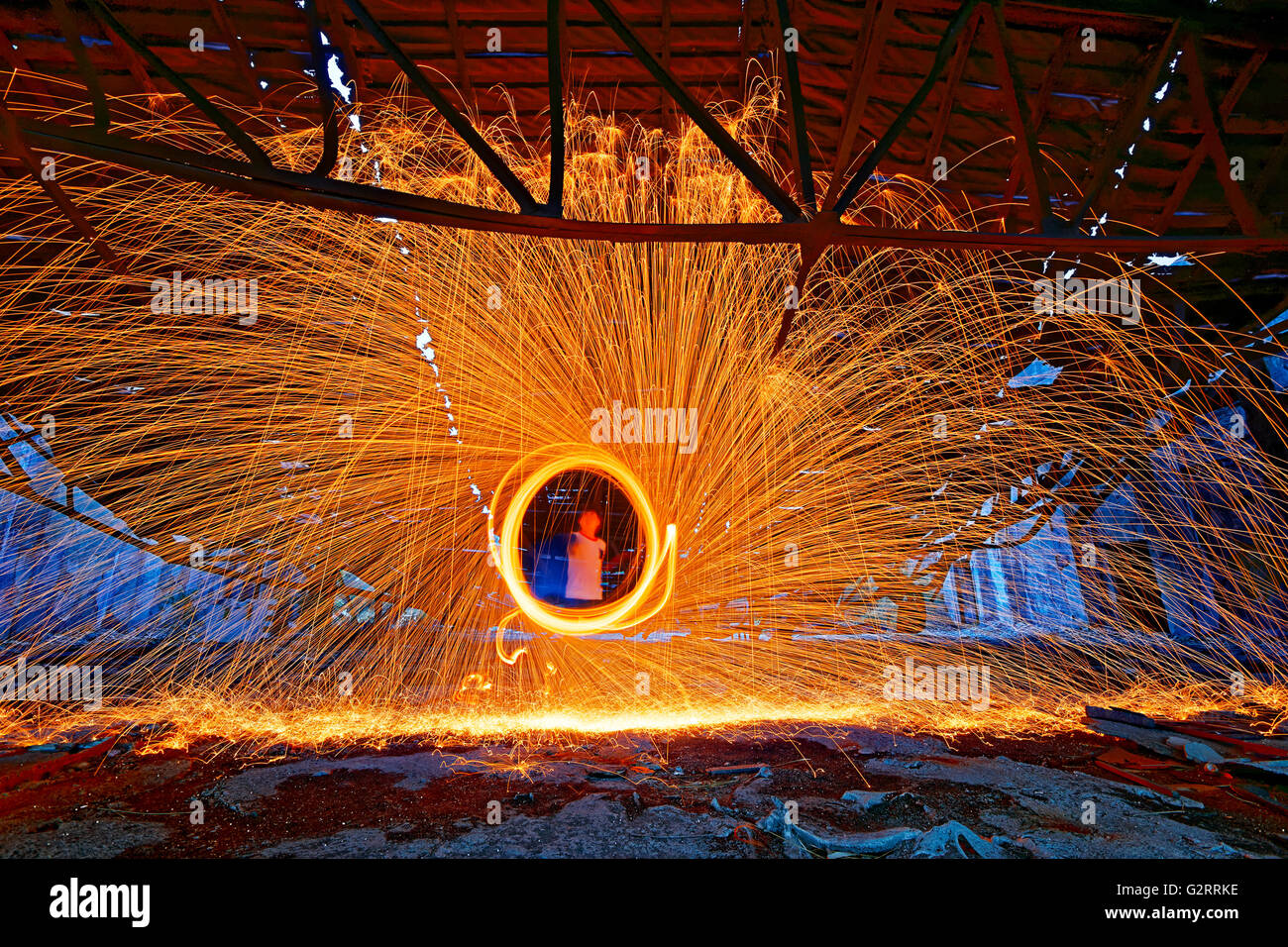 Burning Steel Wool spinning. Showers of glowing sparks from spinning steel wool in ruins Stock Photo