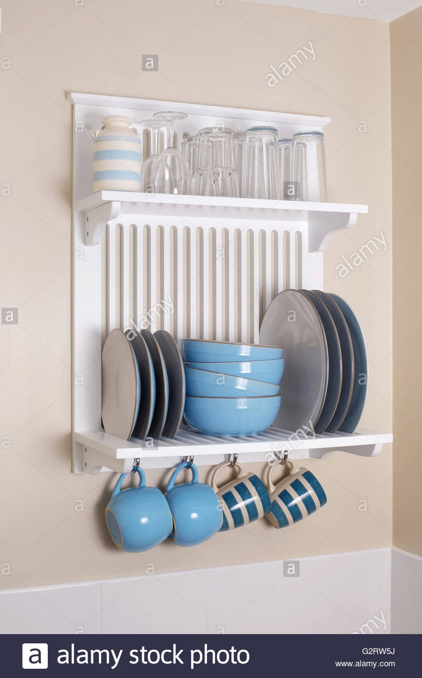Crockery plate rack and shelves mounted on kitchen wall - Stock Image