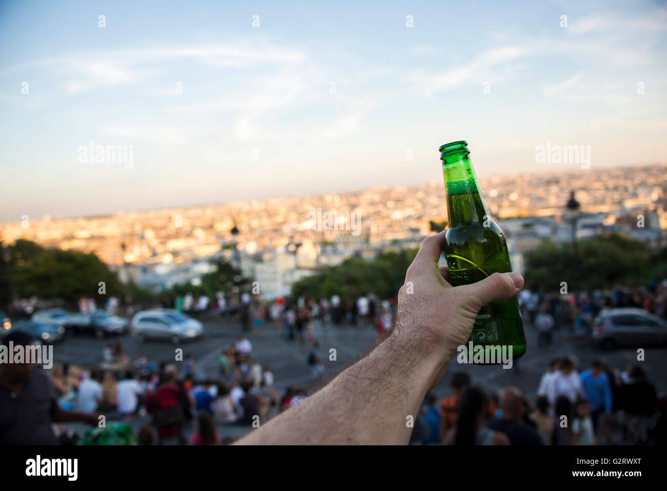 A hand grabing a beer in the ambience of a very crouded staircase in Montmatre, Paris, France. Stock Photo