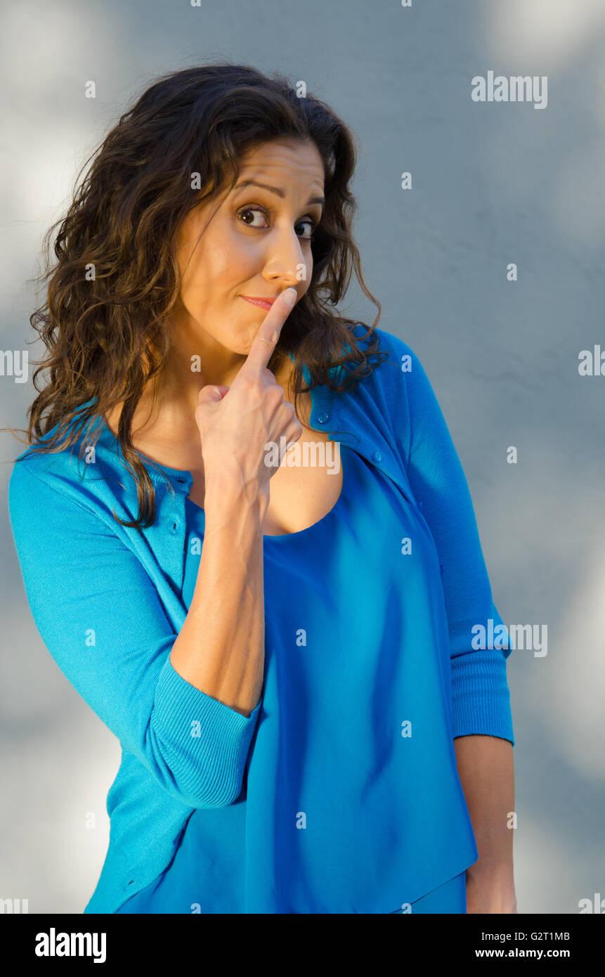 Hispanic woman with finger on lips - Stock Image