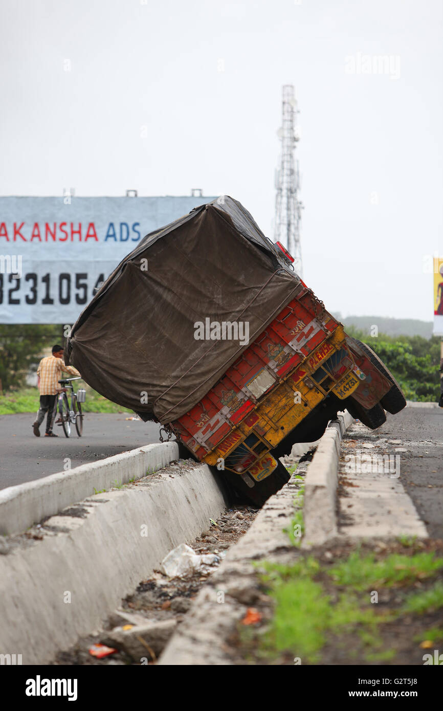 A truck toppled over into a drainage line during a freak accident in India. Stock Photo