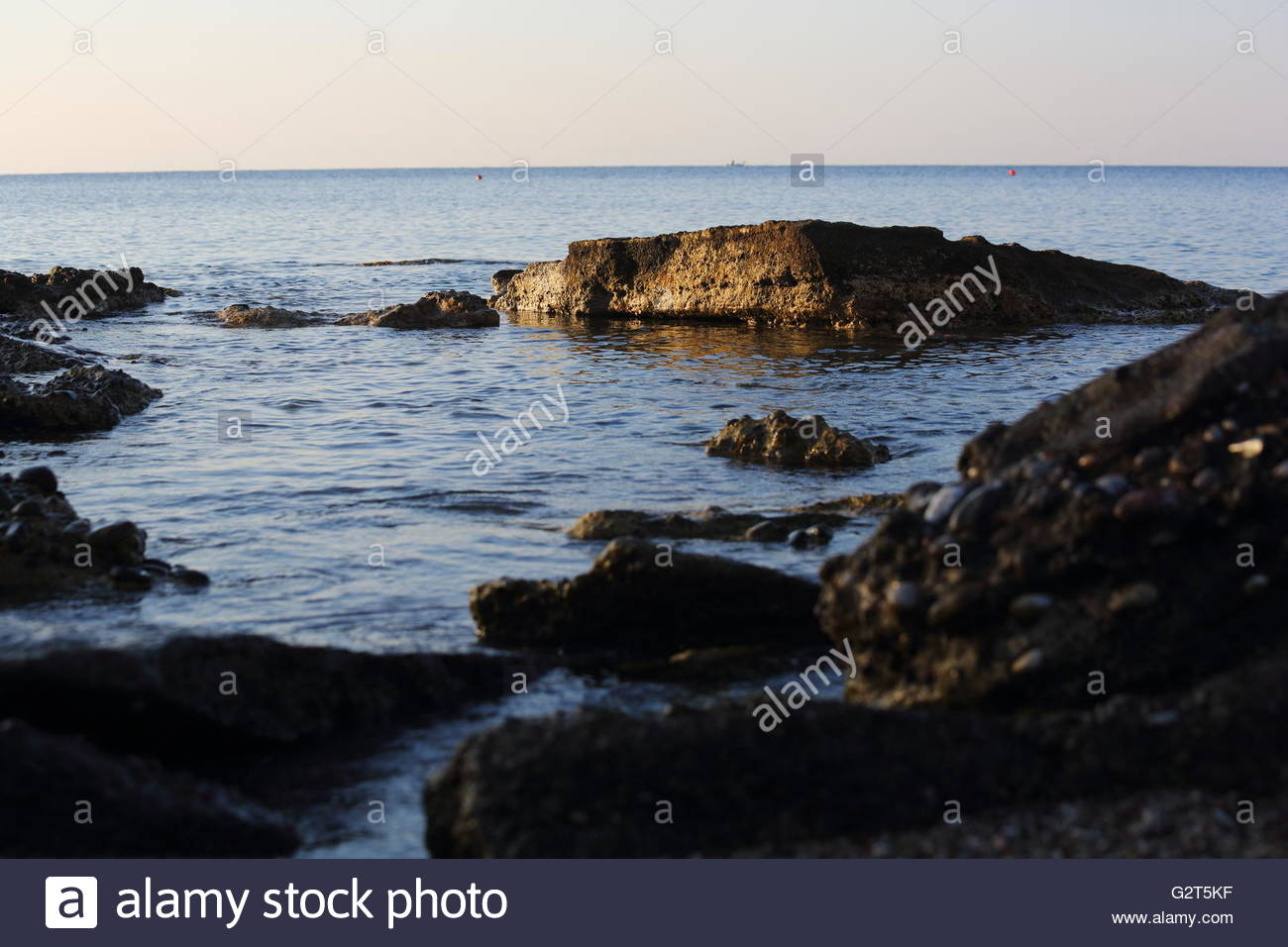 Dawn breaks across rocks in a bay  on the island of Rhodes in greece - Stock Image