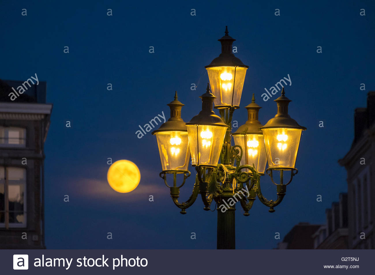 Full moon rising behind street lamps, Maastricht, Limburg, Netherlands - Stock Image