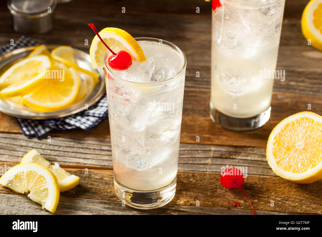 Refreshing Classic Tom Collins Cocktail with a Cherry and Lemon Slice - Stock Image