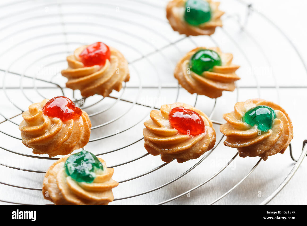sicilian almond pastries with candied cherries on cake rack - Stock Image