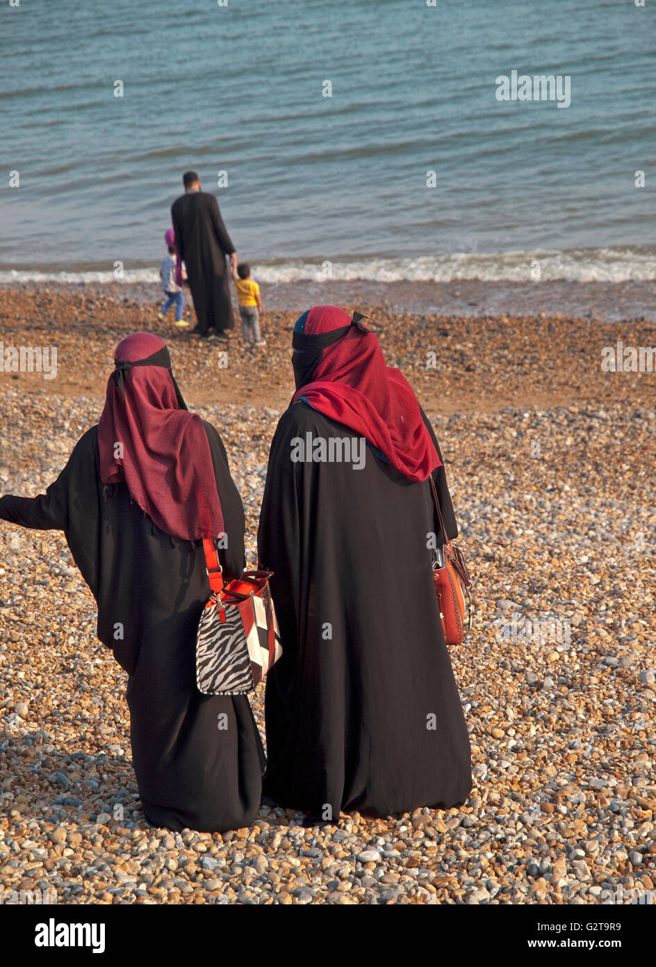 Burka clad Muslim women on Brighton beach - Stock Image