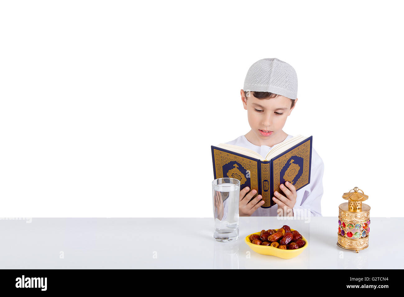 Young Muslim boy reading Quraan in Ramadan - sitting at a table with water , dates , Quran, and Ramadan lantern - Stock Image