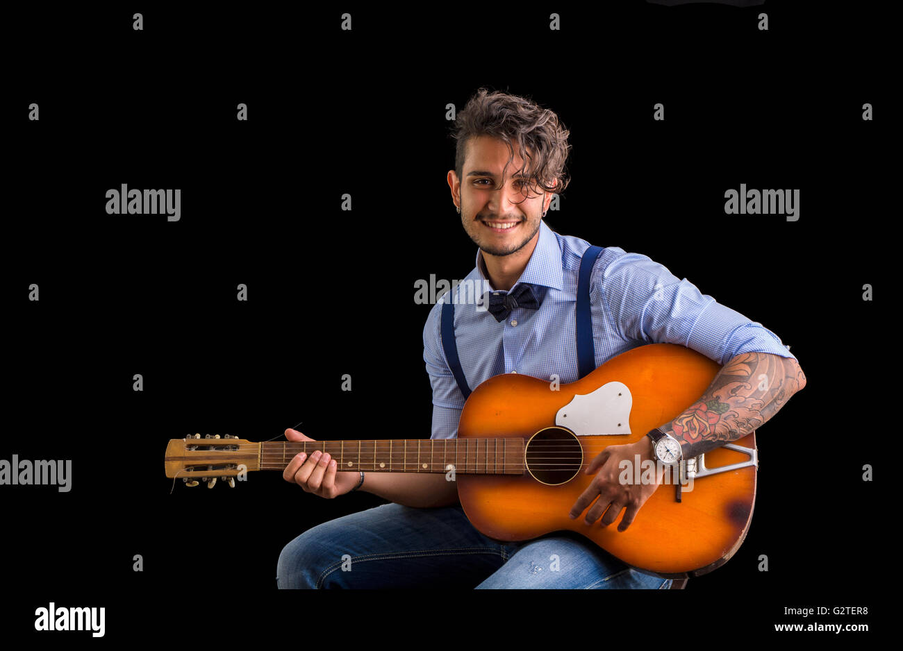 Handsome young man in bow-tie with guitar looking at camera.Studio shot. - Stock Image