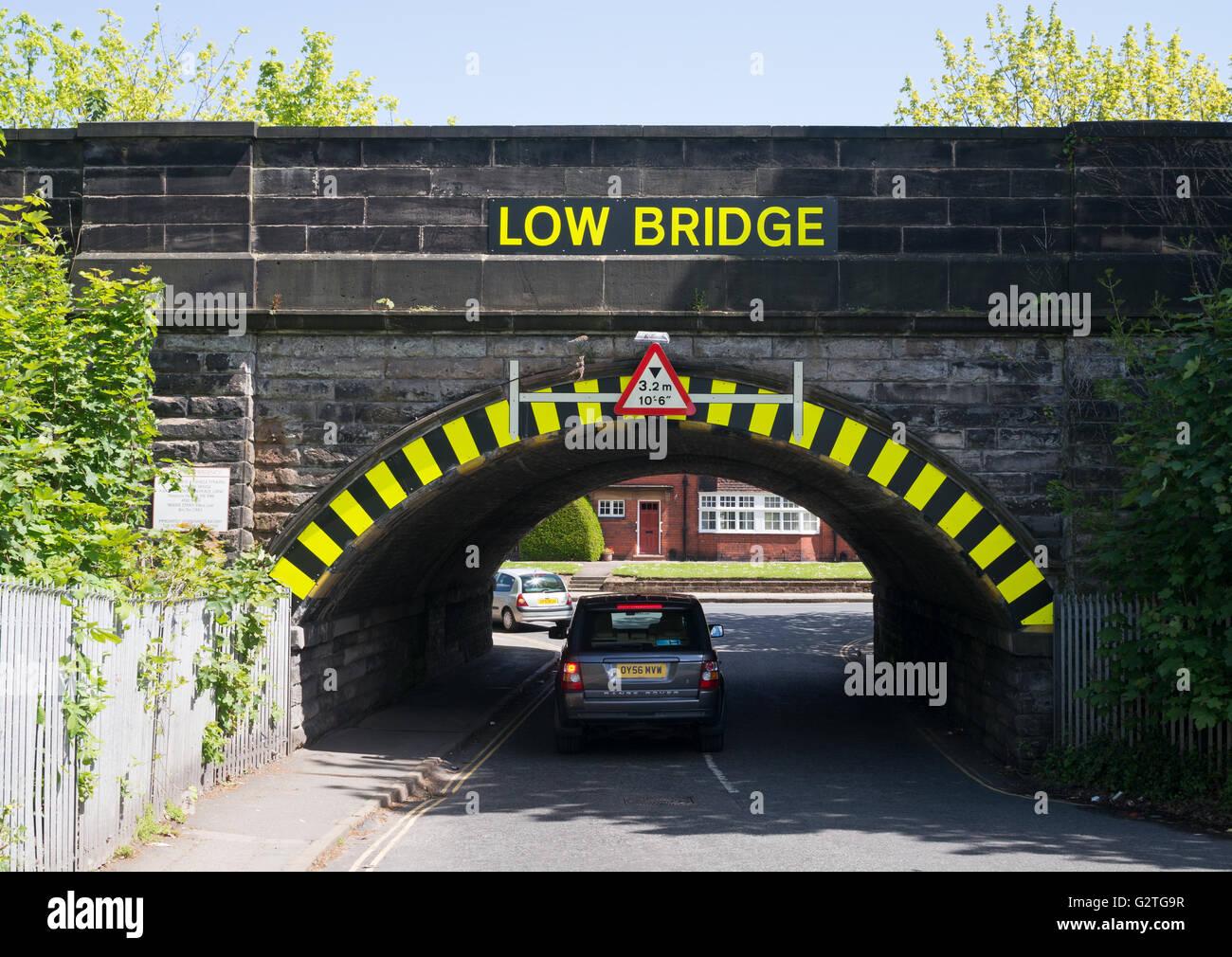 Car passing under low railway bridge over Ellen's Lane, Port Sunlight , Merseyside, England, UK - Stock Image