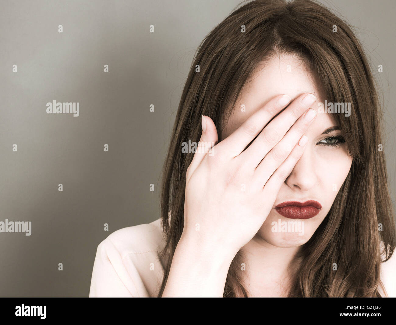 Creative Portrait of a Young Caucasian Woman Covering Her Right Eye With Her Hand Looking Miserable and Concerned - Stock Image