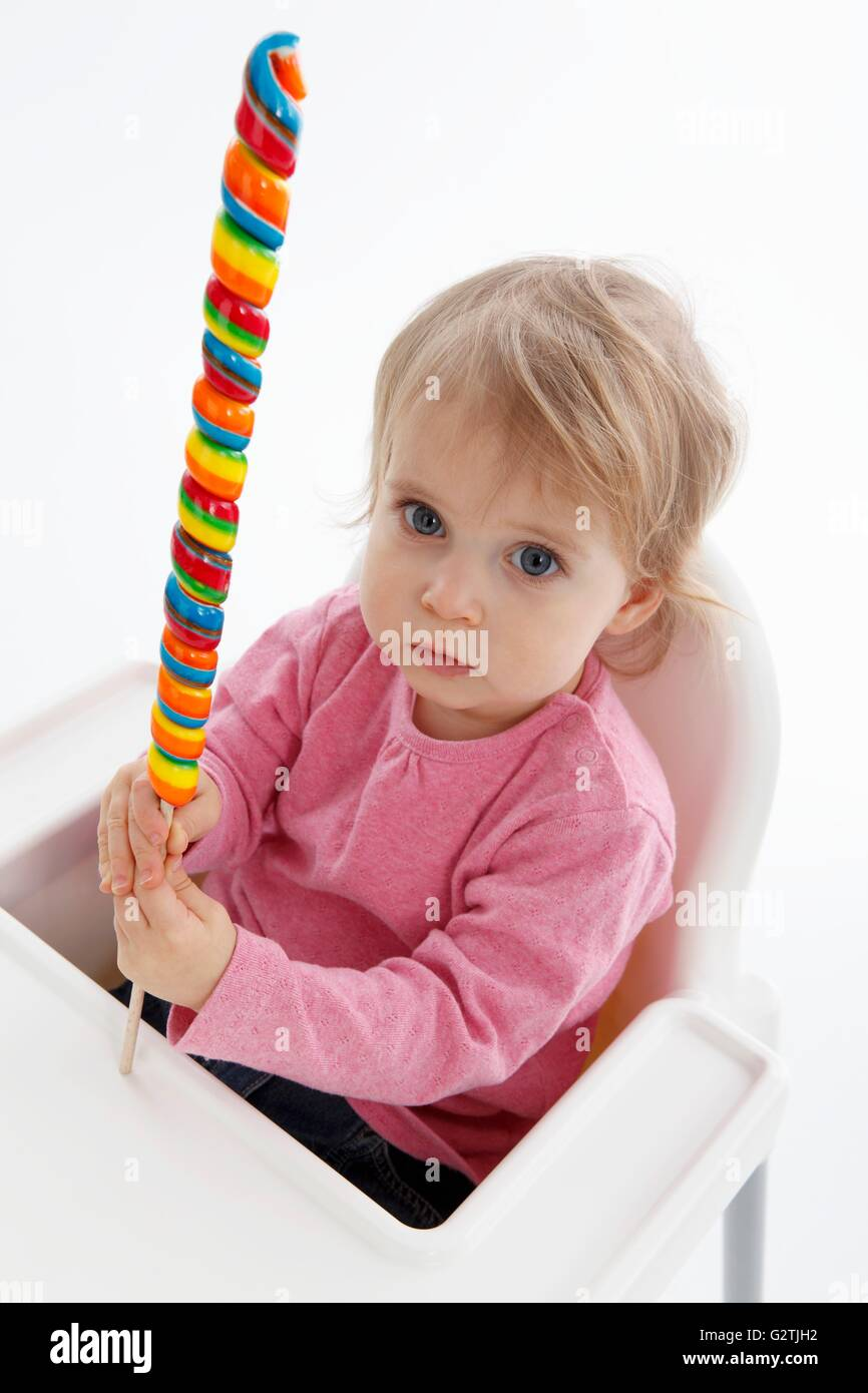 A small child holding a giant lolly - Stock Image