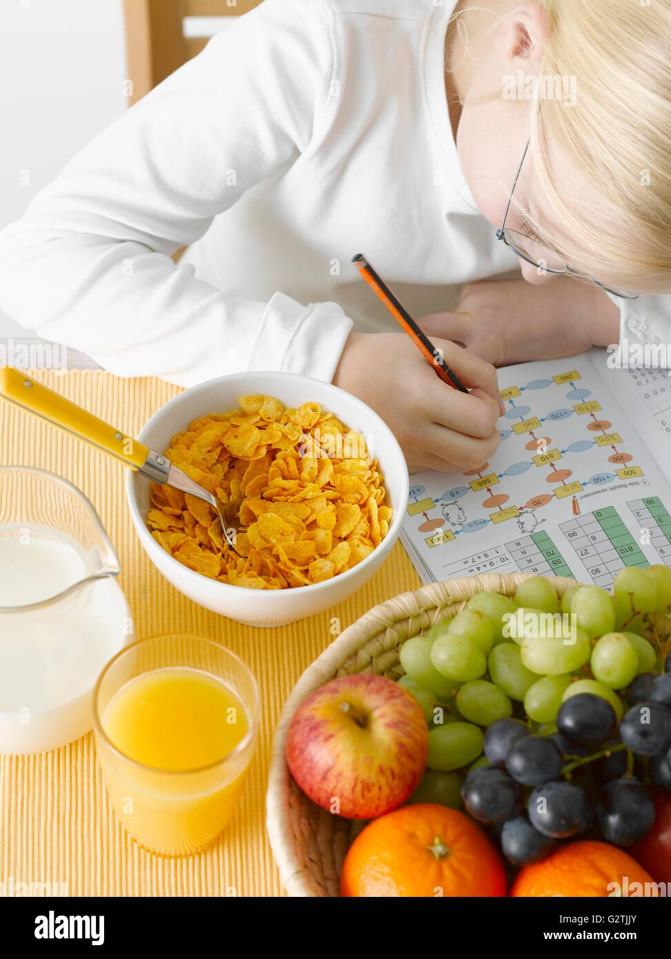 Girl with exercise book in front of healthy breakfast - Stock Image