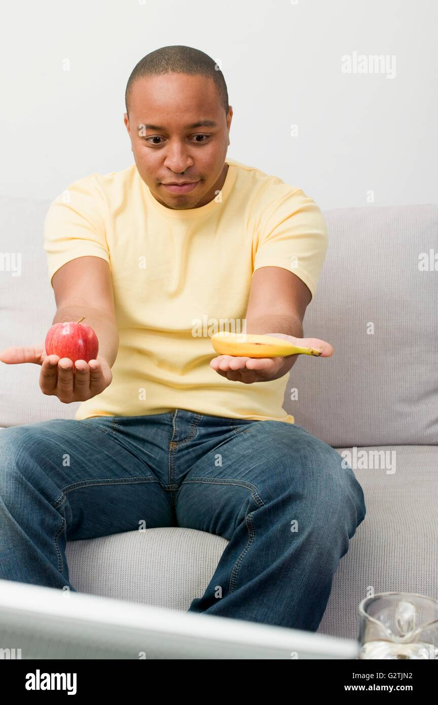 Young man with apple and banana watching TV - Stock Image