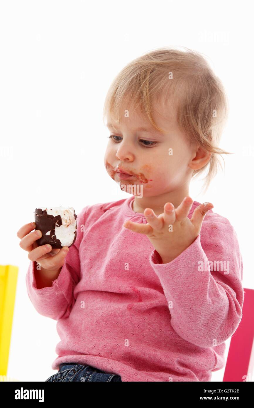 A small child eating a chocolate marshmallow - Stock Image