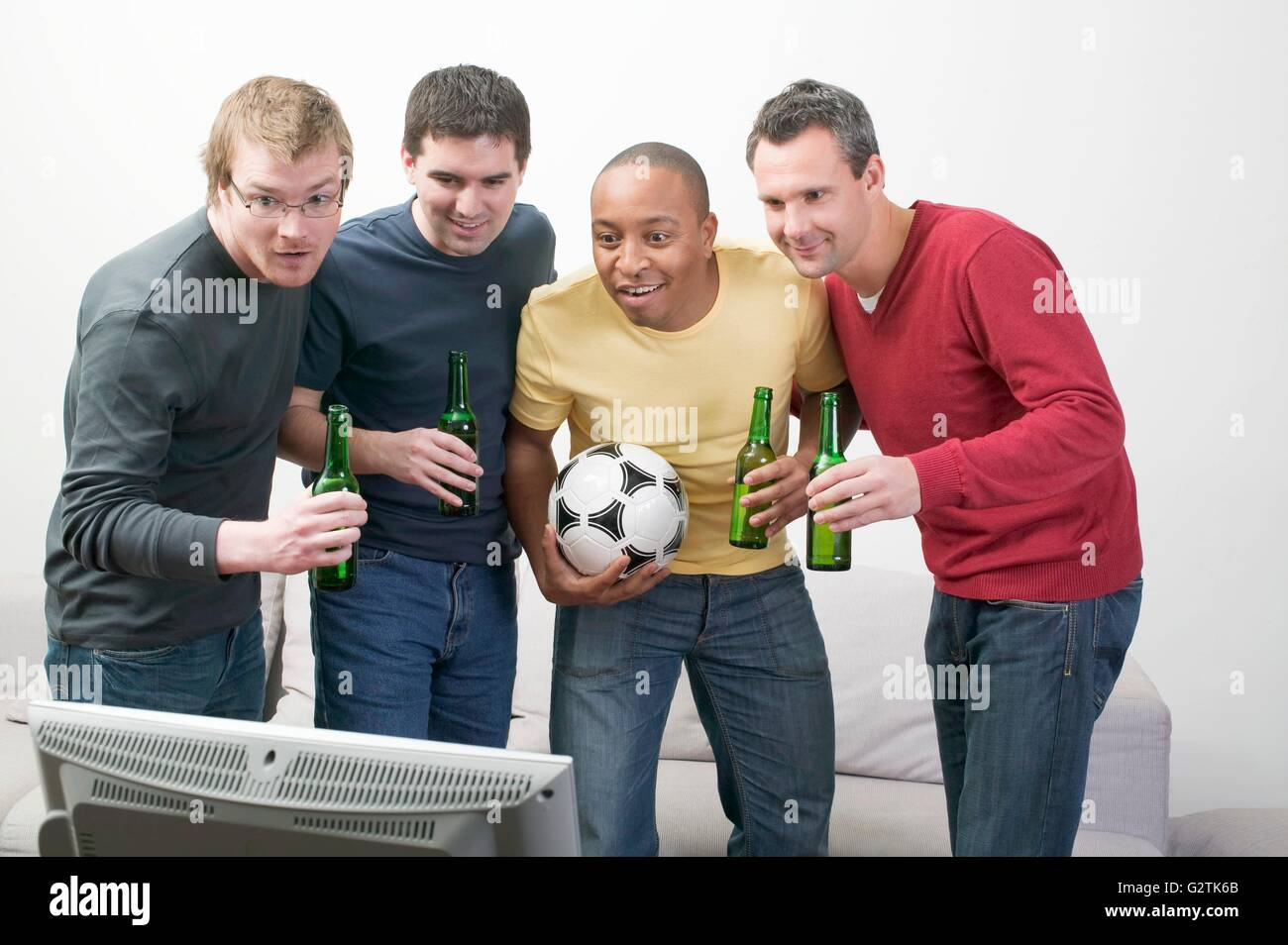 Four men with bottles of beer and football in front of TV - Stock Image